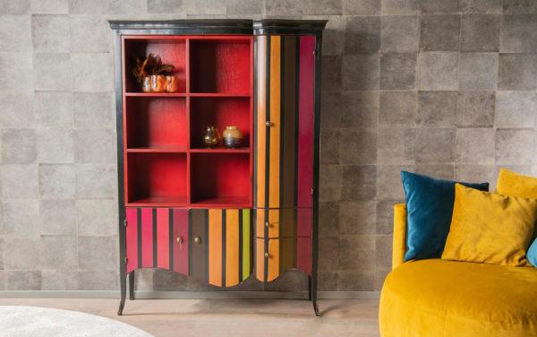 gekleurde open vakken boekenkast met strepen onder deurtjes en lades